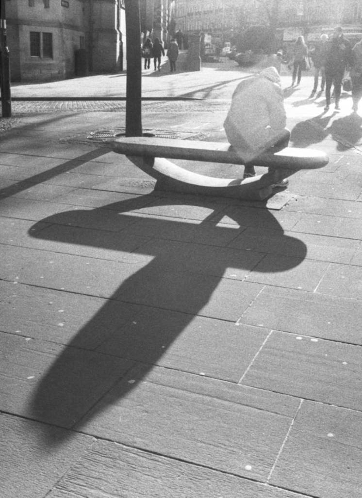 Elongated shadow of man sat on a bench in Sheffield