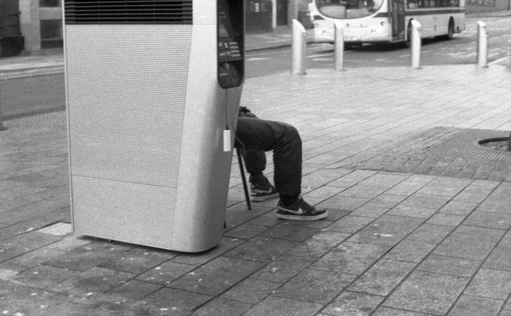 A man charging his phone at a BT InLink hub in Sheffield