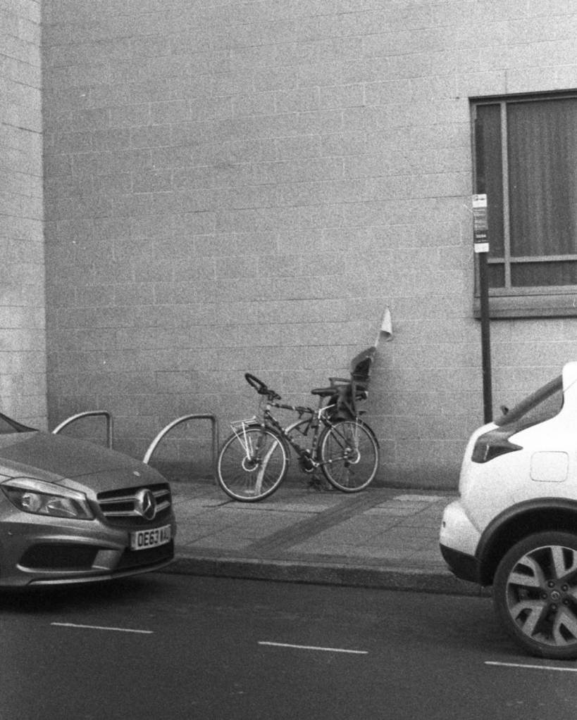 Bicycle with child seat and flag parked between two cars