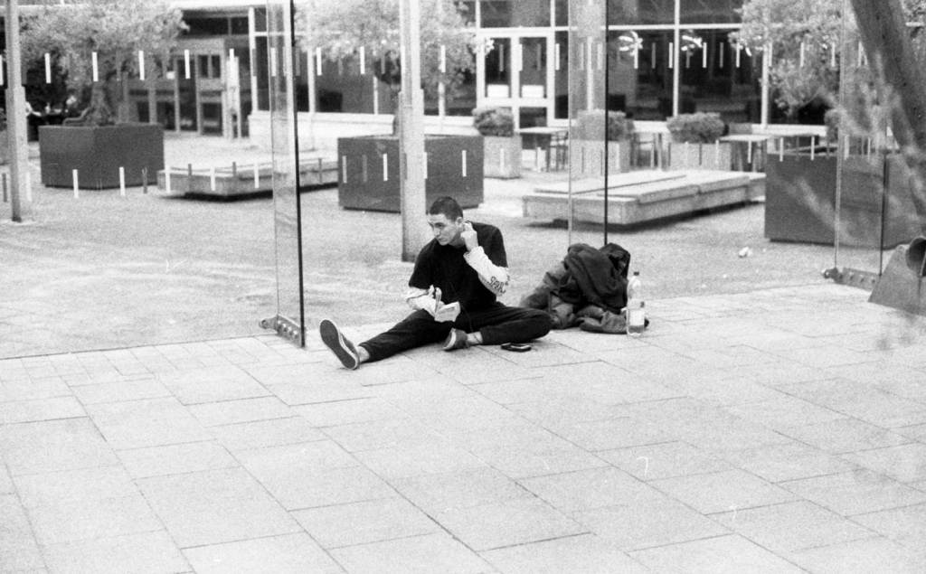 Boy stretches and reads in Sheffield Winter Gardens Street Photography