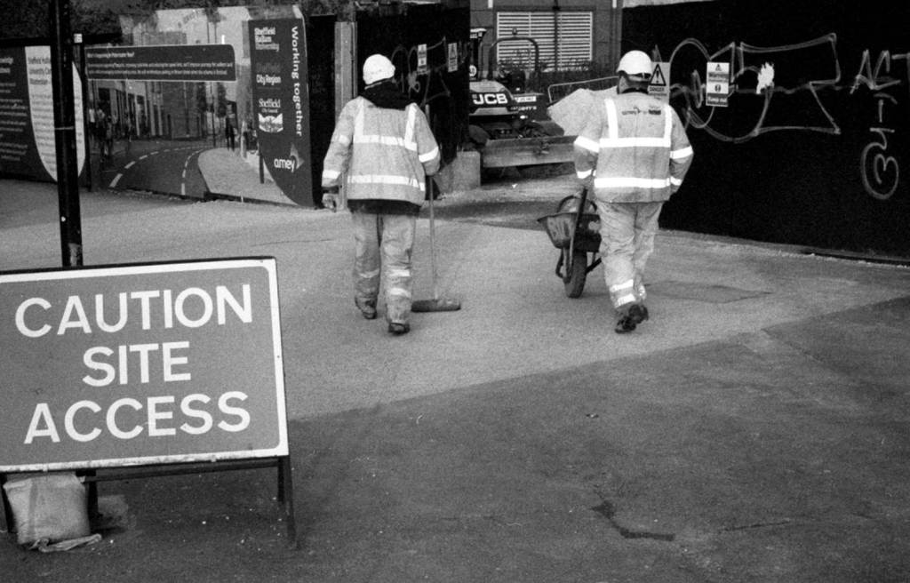 Workmen access construction site in high visibility clothes and hard hats