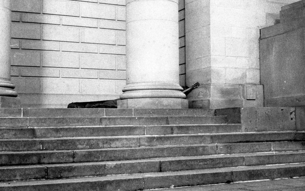 Homeless Person sleeps on Sheffield city hall steps With guitar