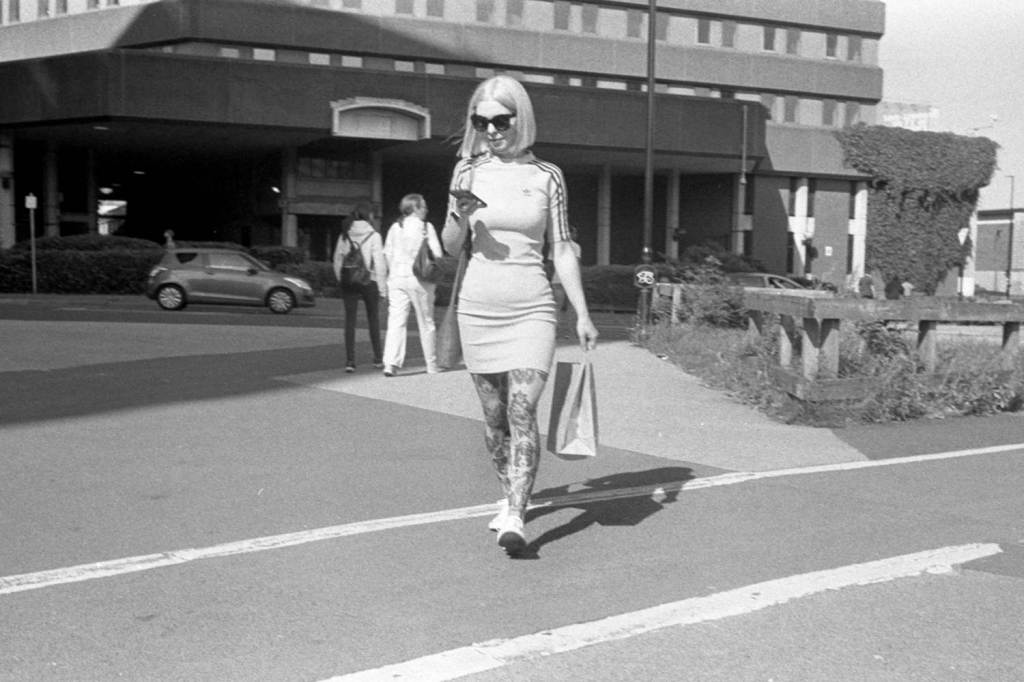 Stylish woman with tattoos and sunglasses checks her phone walking through Sheffield