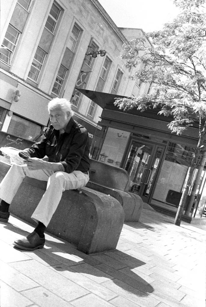 Vintage style old man sat on bench reading a newspaper