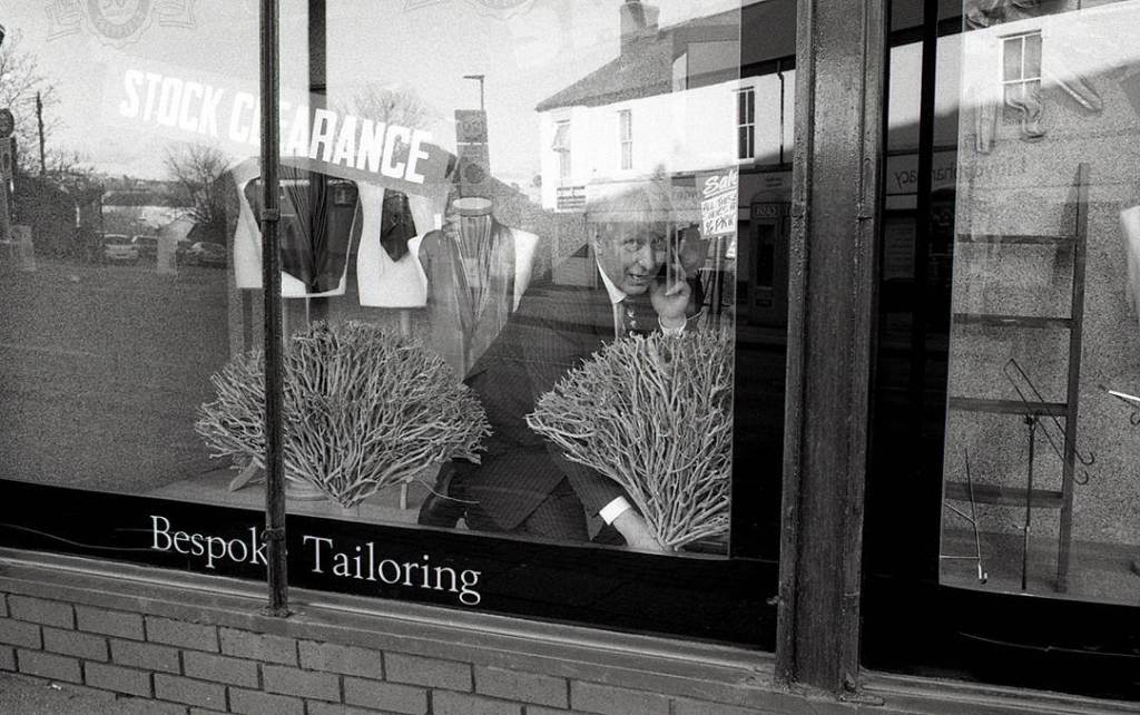 Man decorates window of tailored suit shop on London road Sheffield