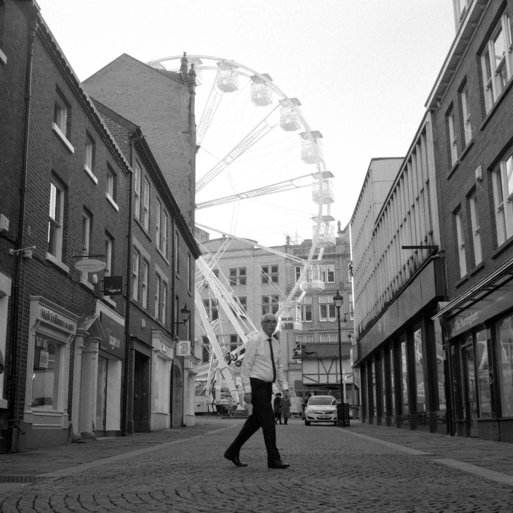 Smartly dressed Man walks through Sheffield City Centre with Ferris wheel in background