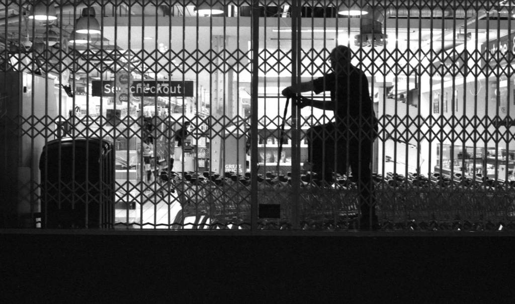 Man adjusts protective shutters on supermarket windows at closing time