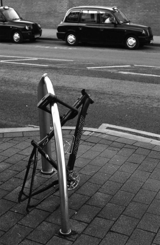 Bicycle with stolen wheels and parts locked up with Taxis in background
