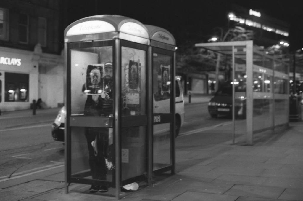Man applies posters to phone booth windows